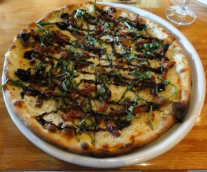 Pizza with sun-dried tomatoes, basil and balsamic reduction