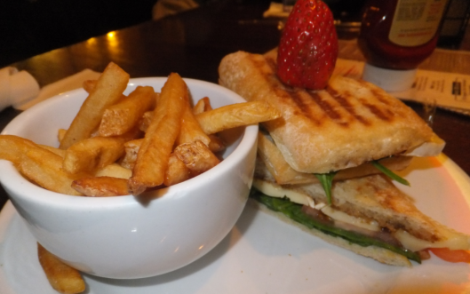 Grilled brie paniniwith spinach, caramelized onions, and tomato on ciabatta