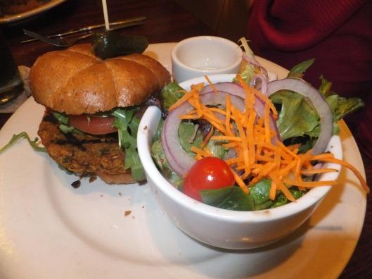Homemade vegan burger served with arugula, avocado, and tomato on a wheat bun