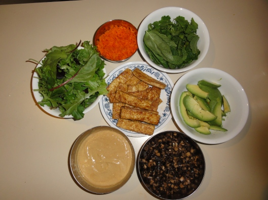 Salad greens, Carrots, herbs, avocado, mushrooms, peanut sauce, and tofu in the middle