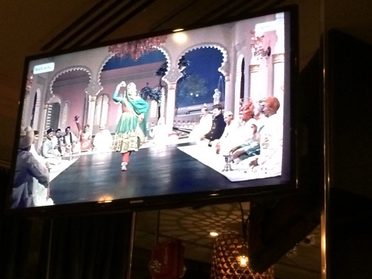 Classic Bollywood dance numbers play above the bar